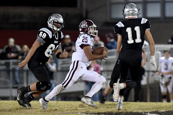 Swain County's Damian Lossiah runs the ball against Robbinsville's Rossi Wachacha, left, and Seth Lawson during their game in Robbinsville on Oct. 28, 2019.