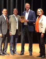 Former Lakeview standout Adam Norlander (with plaque) was inducted into the Kalamazoo College Hall of Fame.