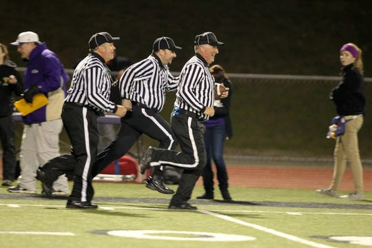 Steve Lingenfelter leads a group of football officials in a warm-up before a game. Lingenfelter has been a referee for high school games since the 1990s and still works most Friday nights.