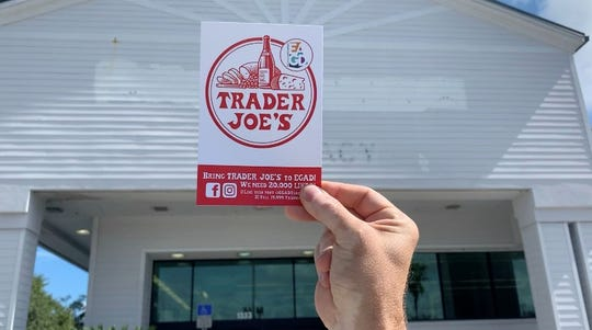 Derek Gores holds up a Trader Joe's logo to show what it would look like on the former Walgreens building in Eau Gallie.