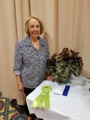 Dianna Zaebst stands beside her Best of Show horticulture entry, a Nautilus Supreme begonia, at the region 7 fall flower show at Ashland University.