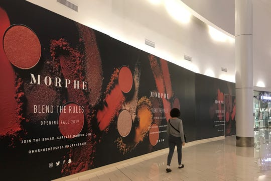 Workers are preparing a Morphe store behind a colorful partition at Cherry Hill Mall.