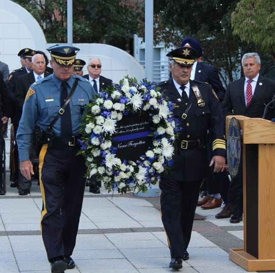 Sheriff Frank Provenzano and Colonel Patrick Callahan place a wreath alongside the memorial