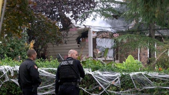 Woodbridge Township police officers are shown near one of the two homes that were severly damaged after a plane crash into them on Berkeley Avenue in the Colonia section of Woodbridge Tuesday, October 29, 2019.