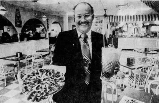 """Happy"" Joe Whitty shows off his pizza and giant soda at his pizza parlor and soda fountain at Southridge Mall in a Des Moines Sunday Register article published on May 16, 1976."