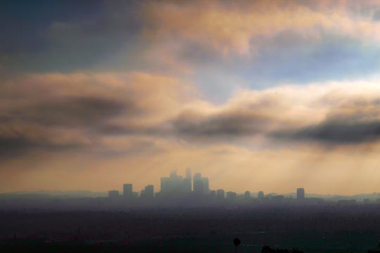 In this Oct. 26, 2018, file photo, downtown Los Angeles is shrouded in early morning coastal fog and smog. General Motors, Fiat Chrysler, Toyota and many others in the auto industry are siding with the Trump administration in a lawsuit over whether California has the right to set its own greenhouse gas emissions and fuel economy standards.