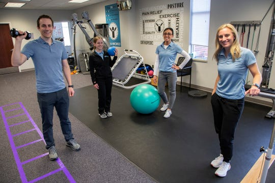 Physical therapist Alex Pieters, left, poses with his colleagues Lindsey Amato, Maria McCabe and clinic director Katie Hrisoulis at Team Rehabilitation on Thursday, Oct. 24, 2019 at their Macomb Township location.