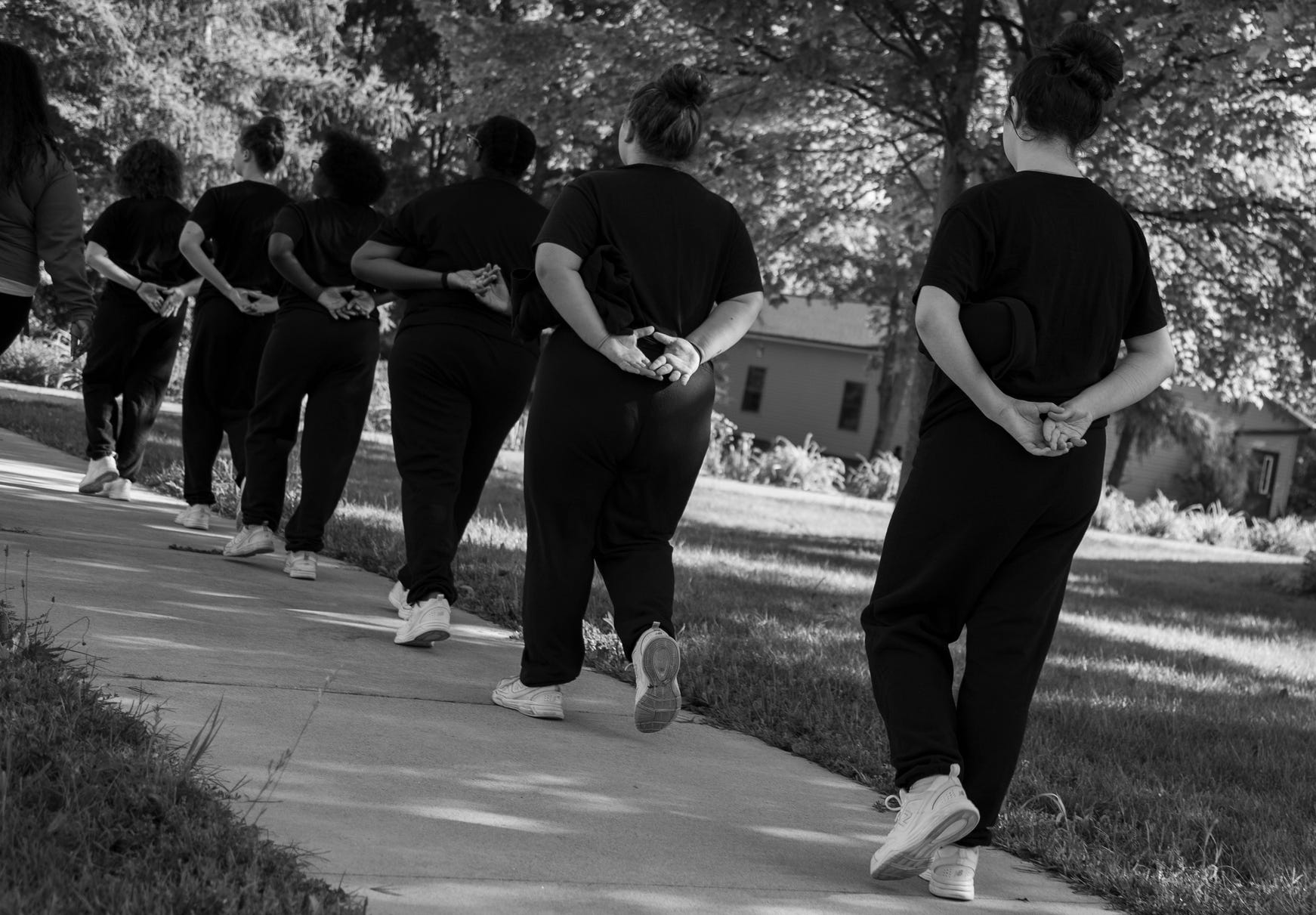"""Clients line up in a regimented way to be escorted across campus at the Wolverine Growth and Recovery Center in Vassar Monday, Aug. 28, 2019. Each client has to remain at arms length and hold their hands in a """"diamond"""" shape behind their backs."""