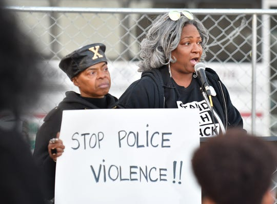 Akouwa Loko, left, of Detroit holds a sign while Consuelo Lopez speaks at the protest to demand justice after Atatiana Jefferson of Texas was killed by a white police officer.