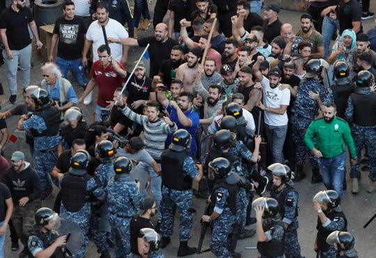 Riot policeman try to stop Hezbollah supporters who arrived to burn and destroy tents in the protest camp set up by anti-government protesters near the government palace, in Beirut, Lebanon, Tuesday, Oct. 29, 2019.