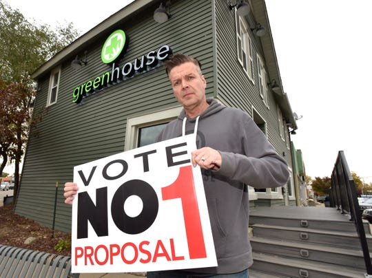 Greenhouse Walled Lake owner Jerry Millen poses in front of his medical marijuana facility on the corner of Walled Lake Dr. and Pontiac Trail, Friday afternoon, October 25, 2019, holding a Vote No Proposal 1 sign.