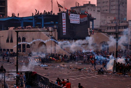 Anti-government protesters gather while Iraqi security forces fire tear gas during a demonstration in Tahrir Square in Baghdad, Iraq, Monday, Oct. 28, 2019.