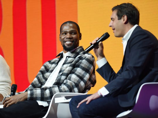 NBA star Kevin Durant, left, listens to moderator Steven Bertoni, VP & Senior Editor of  Forbes during the lunch session Tuesday at the  Forbes Under 30 Summit in Detroit.