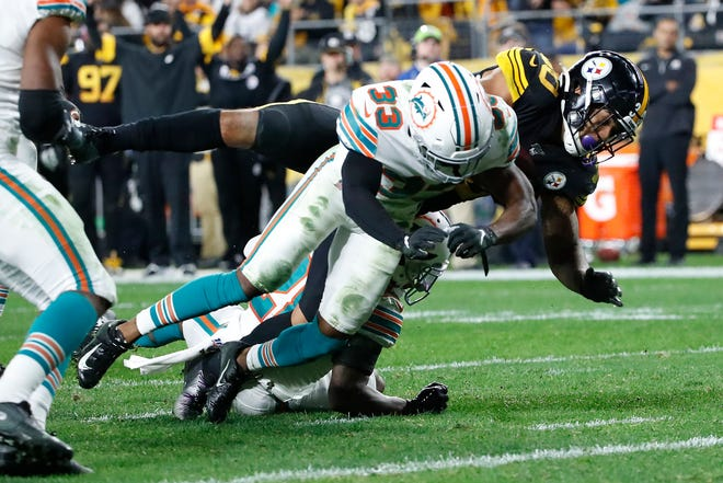Pittsburgh Steelers running back James Conner (30) dives for the end zone for a touchdown with Miami Dolphins cornerback Jomal Wiltz (33) defending during the second half.