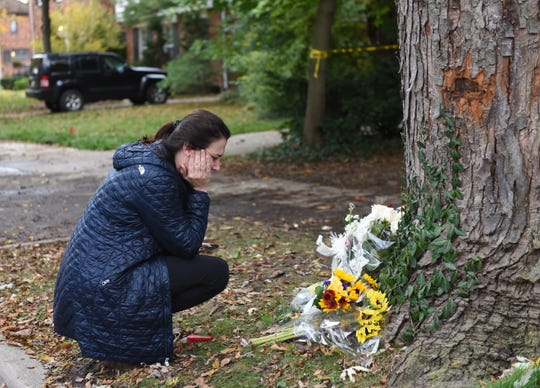 Linda Thom of Grosse Pointe, who knew  Walter Briggs Connolly, 11,  and his brother Logan, 9,  pays her respects at the memorial site in front of their home.