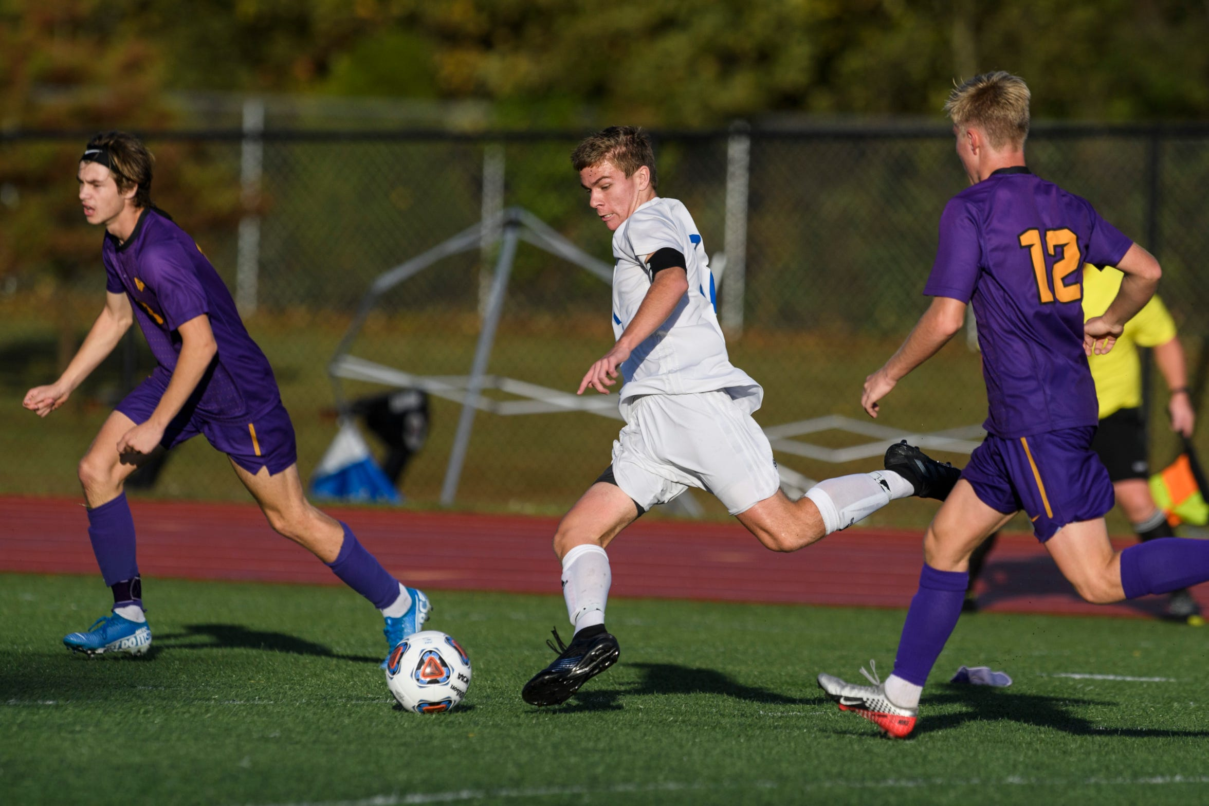 Memorial's Isaac Bennett (11), center, drives the ball down the field during the IHSAA Class 2A semistate matchup against the Guerin Catholic Golden Eagles at Bundrant Stadium in Evansville, Ind., Saturday, Oct. 26, 2019. After double-overtime and a penalty-kick battle, the Tigers defeated the Golden Eagles 3-2 to advance to the 2A state championship.