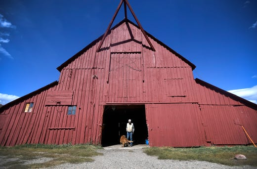 Jay Fetcher stands in the doorway of his barn with his Golden Retriever at his Clark Ranch north of Steamboat Springs, Colo. on Wednesday, Oct. 9, 2019.