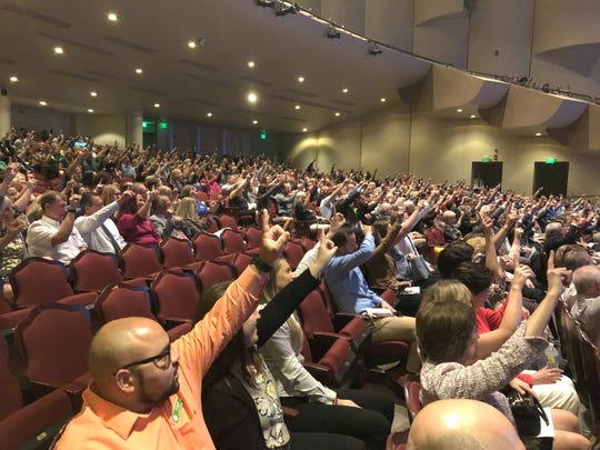 "Community members at the event raise their hands and chant, ""One way, United Way,"" at the campaign kickoff event on Oct. 29, 2019, in Fort Myers."