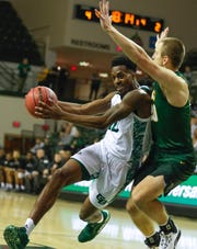 University of Wisconsin-Green Bay forward Josh McNair (12) drives to the basket while St. Norbert forward Nolan Beirne (20) defends him during their basketball game on Monday.