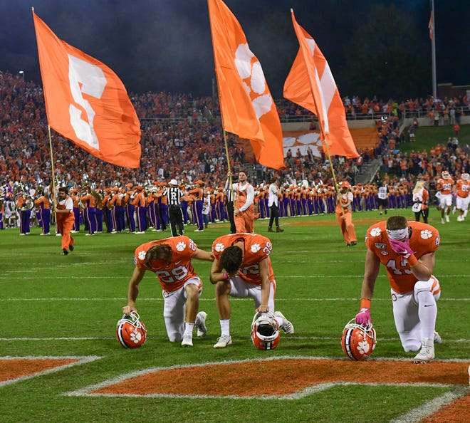 Clemson punter Aidan Swanson(39), left, kicker B.T. Potter (29), and linebacker Chad Smith (43) kneel in the end zone before the game at Memorial Stadium with Boston College in Clemson, South Carolina Saturday, October 26, 2019.
