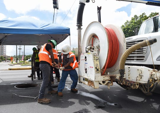 Guam Waterworks Authority employees operate a vacuum truck for bucket cleaning during continued work on a 36-inch main sewer line in Hagåtña on Tuesday.