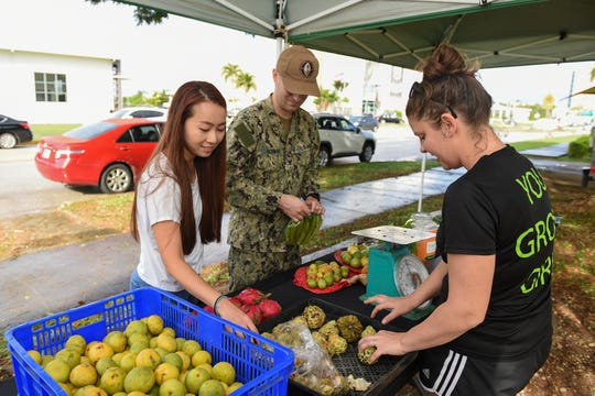 Farm to Table Guam Corp. regulars Midori and Josh Schwab shop through the organic selection of produce with the assistance of project director Cassie Brady, right, in Hagåtña, Oct. 29, 2019.