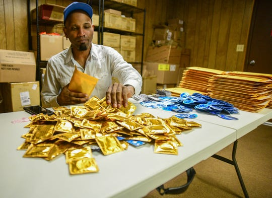 AIDS Services Coalition outreach worker Brian Outlaw packages condoms Tuesday, Oct. 29, 2019, at the ASC office in Hattiesburg. The free condoms will be mailed to throughout the state to those 13 and older who request them.