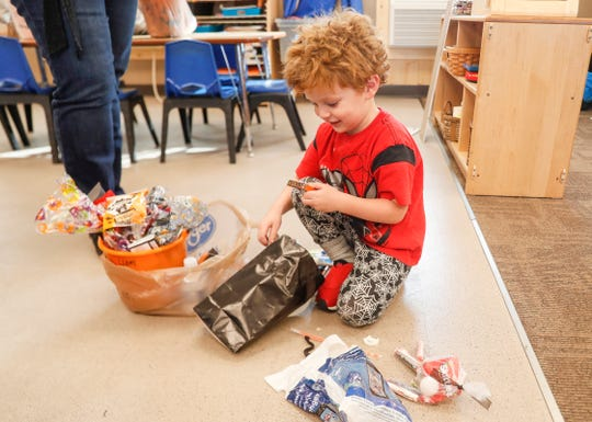 Liam Clinger digs through a bag of candy and shows his mother Jeannie Bellmar at Concord Neighborhood Center, Thursday, Oct. 24, 2019, Indianapolis.