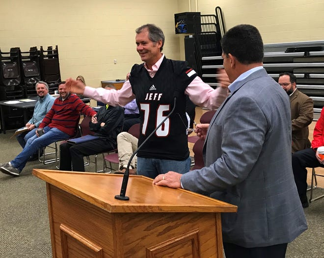 West Lafayette John Dennis, left, shows off a Lafayette Jeff football jersey, the payoff for a friendly bet he lost to Lafayette Mayor Tony Roswarski after Jeff beat West Lafayette, 74-66, to open the season on Aug. 23. Dennis, a West Lafayette grad, and Roswarski, a Lafayette Jeff grad, are 1-1 on their bets since the schools renewed their rivalry in 2018. Roswarski brought the jersey for Dennis to the West Lafayette board of works meeting at the former Happy Hollow Elementary on Tuesday, Oct. 29, 2019.