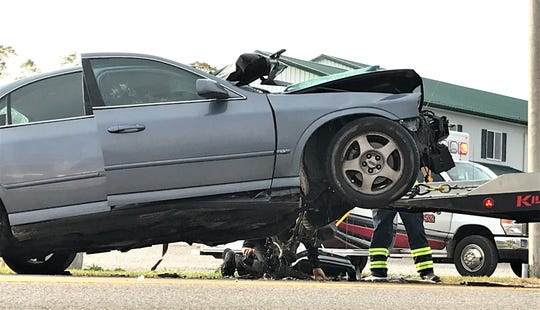 Ohio Highway Patrol Trooper RJ Wilson examines the undercarriage of a car involved in a two-car crash Tuesday morning.  The Ohio Highway Patrol confirmed both drivers were killed in the crash.