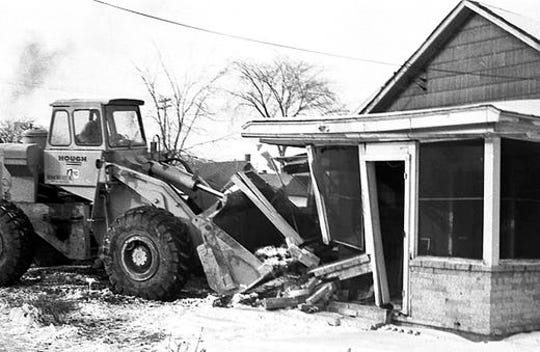 A bulldozer demolishes a home as part of the connector route clearance for I-496 in January 1966.