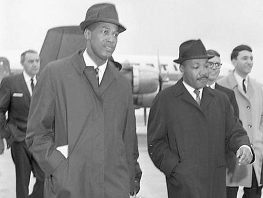 Dr. Martin Luther King Jr. arrives at the airport in Lansing on Feb. 11, 1965. He is accompanied here by MSU education professor Robert Green (left). King spoke to students at Michigan State University. Dr. Martin Luther King Jr. arrives at the airport in Lansing on Feb. 11, 1965. King spoke to students at Michigan State University.