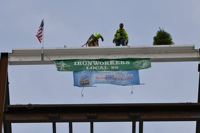 Ironworkers place the final steel beam for McLaren Greater Lansing's new hospital.
