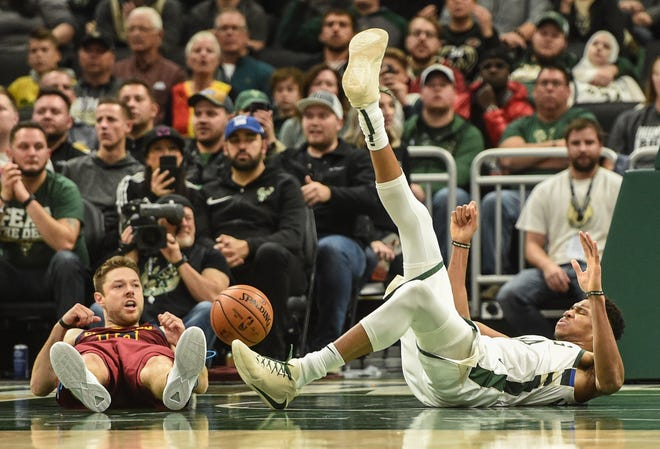 Former teammates Giannis Antetokounmpo and the Cavs' Matthew Dellavedova lay on the court after battling for a loose ball during the fourth quarter