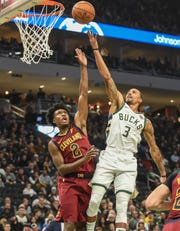 Bucks guard George Hill puts up a finger roll over Cavaliers guard Collin Sexton for two of his 19 points Monday night.