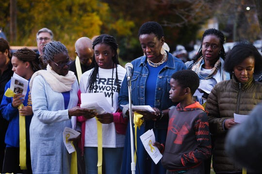 Opeyemi Sowore, (blue jacket), the wife of Nigerian journalist Omoyele Sowore, who is in a Nigerian prison where he has been held since August,  reads a prayer together with her children as Haworth residents gather to demand his release, photographed in front of Borough Hall in Haworth on10/87/19.