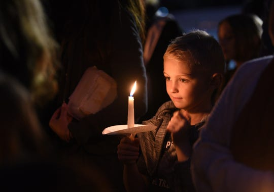 Evan Newson (age 9) holds a lighted candle as he and other Haworth residents gather to demand that local resident and Nigerian journalist Omoyele Sowore be released from a Nigerian prison where he has been held since August, photographed in front of Borough Hall in Haworth on10/87/19.