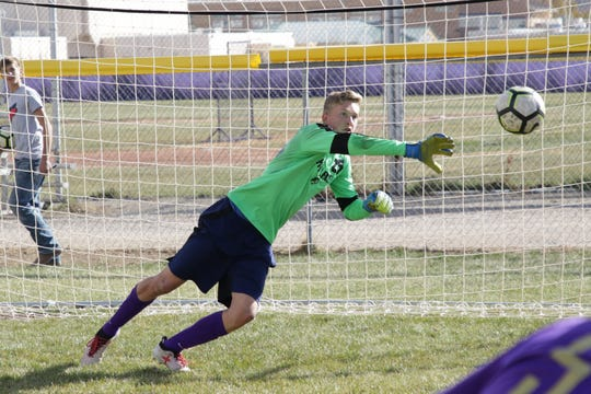 Kirtland Central goalkeeper Ethan Pierro knocks the ball away with his right hand during Tuesday's practice at KCHS. Pierro has 10 shutouts wins in his last 12 matches entering the 4A playoffs.