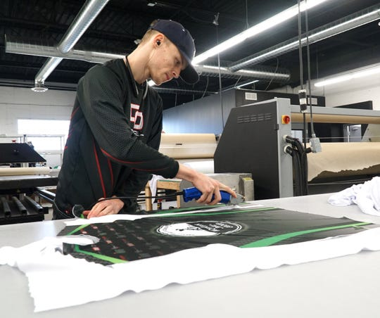 DO Apparel employee Jacob Krasinski uses an electric cutting tool to trim away excess material from jerseys before they're stitched together on Oct. 29.