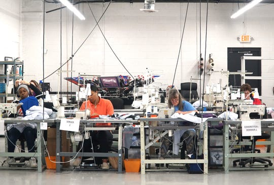 DO Apparel employees man a bank of sewing machines to finish stitching together jerseys at their Livonia location in this 2019 file photo. The company says it's preparing to produce protective masks for health care providers if called upon.