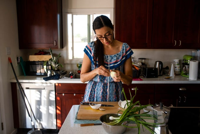 Chef Minerva Orduno Rincon peels an onion to be grilled at her home in Tempe on Thursday, Oct. 24, 2019.