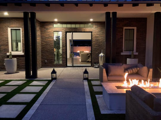 Pavers and artificial grass work in tandem to pull spaces together while defining a pathway to the front door.