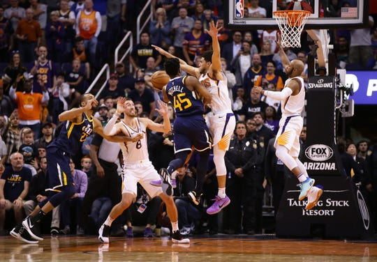 Phoenix Suns guard Devin Booker (1) fouls Utah Jazz guard Donovan Mitchell (45) with .04 seconds left in the game on Oct. 28, 2019 in Phoenix, Ariz. Mitchell made one free throw to win the game 96-95.