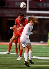 Susquehannock's Nolan Holloway heads the ball away from Caleb Brown of Northern York during the District 3 Class 3-A semifinal game, Monday, October 28, 2019.