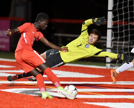 Northern York goal keep John White makes a diving stop on a goal attempt by Fallou Cisse of Susquehannock during the District 3 Class 3-A semifinal game, Monday, October 28, 2019.John A. Pavoncello photo