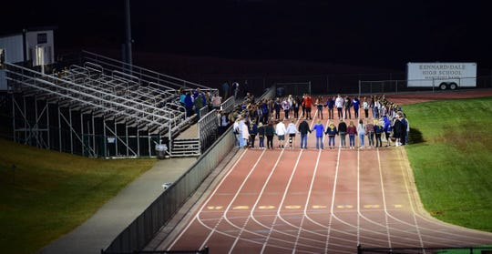 Kennard-Dale students and other members of the community hold hands in prayer for senior student-athlete Patrick Maloney Monday. Maloney suffered a serious head injury in the team's football game this past Friday.