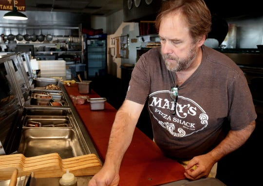 Mary's Pizza Shack employee Rob Byerly prepares food so the darkened Anderson restaurant can open Tuesday, Oct. 29, 2019, using gas-fired ovens and a small generator during a PG&E power outage.