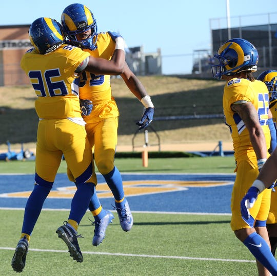 Angelo State University's Dajuan Adkinson (36) celebrates with Simon Maxey after Maxey scored on an interception return against UT Permian Basin during a game at LeGrand Stadium at 1st Community Credit Union Field on Saturday, Oct. 26, 2019. Devin Washington joins in on the celebration.