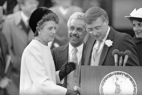 In this Jan. 11, 1986 file photo, Virginia Gov. Gerald Baliles, right, share the podium with Virginia Lt. Governor L. Douglas Wilder, center, and Attorney General Mary Sue Terry, left, after the three were sworn in at the Capitol in Richmond. Baliles died Tuesday, Oct. 29, 2019, at the age of 79 after battling cancer.