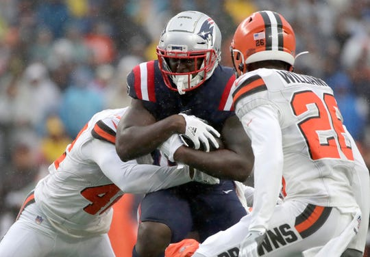 New England Patriots running back Sony Michel, center, carries the ball between Cleveland Browns defenders Morgan Burnett, left, and Greedy Williams on Sunday.